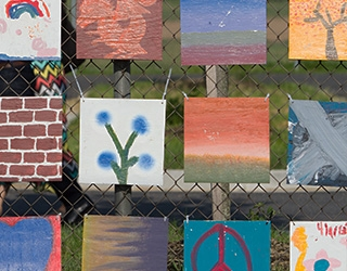 A mural of canvasses displaying student artwork hang on a fence.