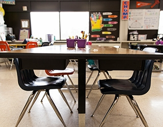 A close up photo of a student worktable with four plastic chairs inside of a classroom; other chairs and classroom materials are in the background, along with decorations on the walls and a large sunny window.