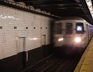 View from a subway platform of a subway train (the A train) driving away from the platform; a large wall of older white subway tile are visible in the background,