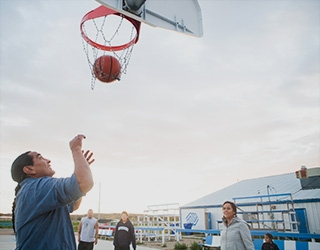 A tall man with a long ponytail stands beneath an outdoor basketball hoop shooting a basketball; a female teacher and two students stand in the background; a Boys and Girls Club small white building is in the background; overhead, there's a grey, cloudy sky.