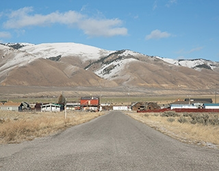 Snowcapped mountains and a blue sky are visible at the end of a long, empty rural road, lined with short buildings and fields.