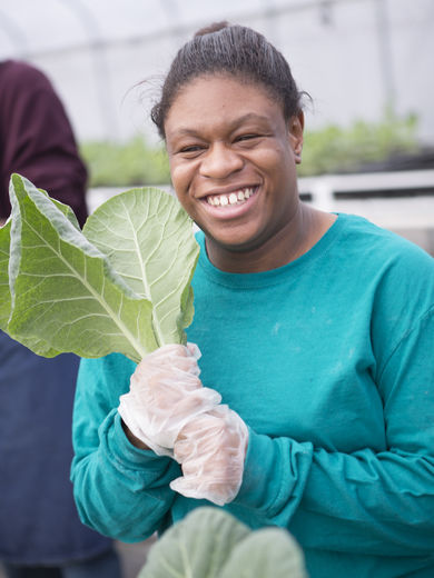 A woman smiling and holding collard leafs