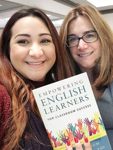 Former student and her teacher holding a book