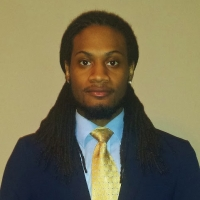 Head shot of a young man with brown shoulder-length dreadlocks and a bearded chin in front of a brown background, wearing a blue blazer, blue shirt, and yellow tie.