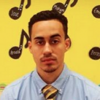 Head shot of a young male teacher with thick black hair, a goatee, a blue shirt, and a yellow tie, in front of a yellow wall with black music notes taped to it.