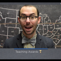 "A young man with short brown hair, a blue blazer, and a bow time smiling in front of a blackboard with a map of the United States on it, with white text on a gray background reading ""Teaching Awards."""