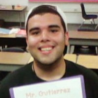 "Head shot of a young man with black hair smiling in a classroom, holding a binder with print saying ""Mr. Gutierrez."""