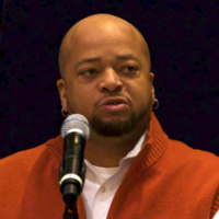 Head shot of a middle-aged man with a shaved head an beard speaking into a microphone, wearing an orange blazer.