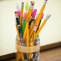 A clear jar filled with eraser-topped pencils sits on a wooden desk.