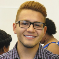 Head shot of a man in his twenties with short blonde hair, smiling, wearing glasses and a grey checked shirt.
