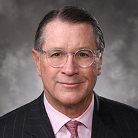 Head shot of a middle aged man, wearing a black suit jacket, pink tie, and glasses