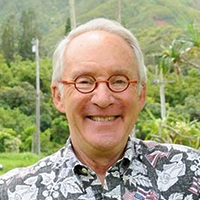 Head shot of an older man with circular glasses and a tropical shirt against a green forestry background.