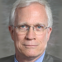 Head shot of an older male, wearing a suit jacket and thin rimmed glasses.
