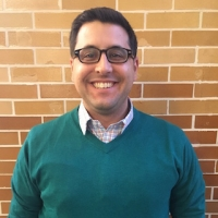 A middle-aged man wearing a green sweater and glasses.