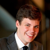 A headshot of a young white man wearing a suit.