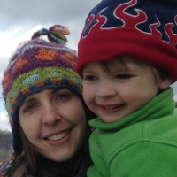 A close shot of a young woman with straight brown hair in a colorful wool winter hat holding a young boy wearing a green sweater and a winter cap with a flame motif.