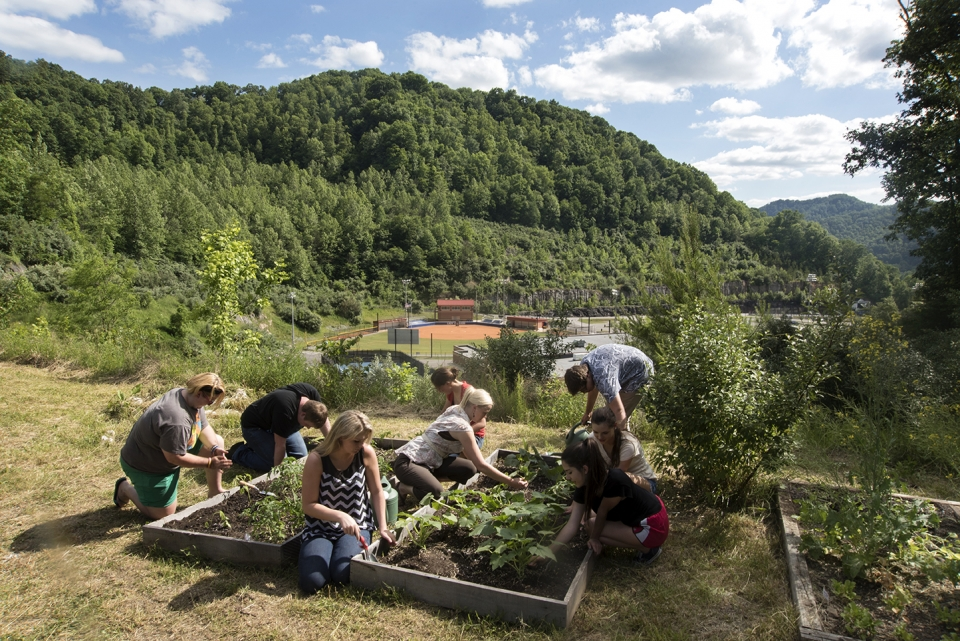 A group of high school students gardening in wooden planters, with a view of rolling, forested hills behind them.