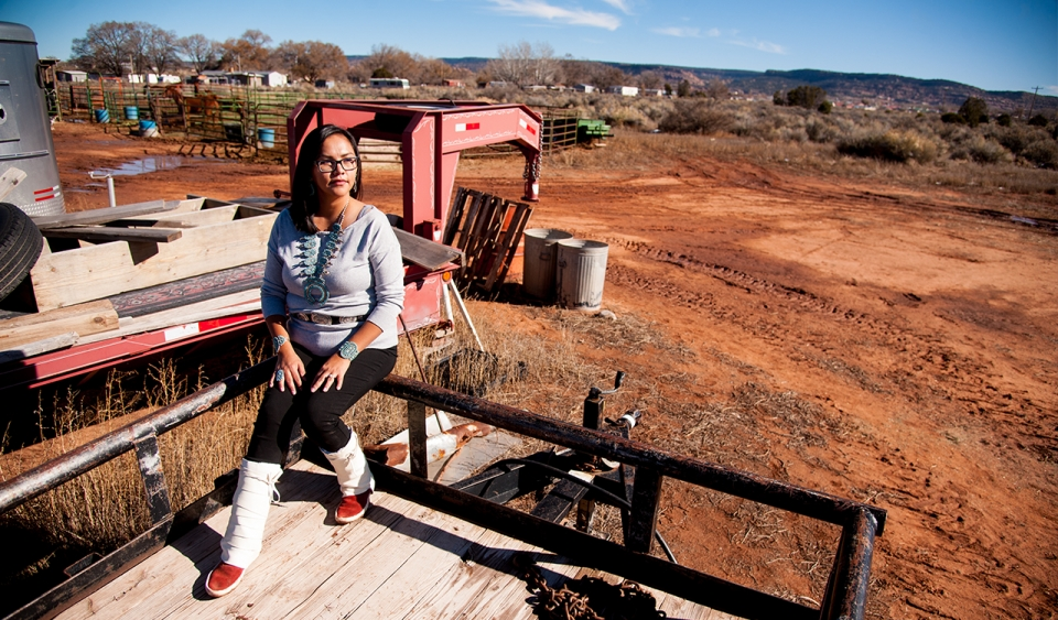 A woman with shoulder length black hair, wearing a gray shirt, black pants, white and red boots, and a large green necklace, sitting in a hitched trailer, with a background of an outdoor construction site.