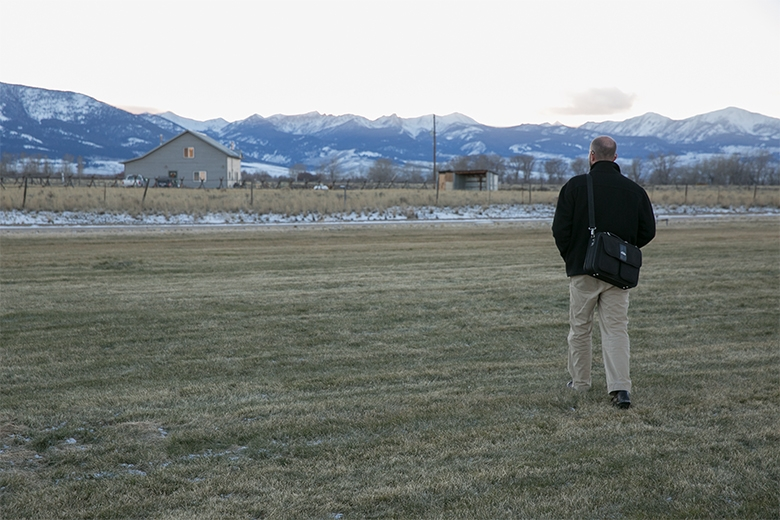A man with a balding head, wearing a black sweater, gray pants and a black messanger bag, walking across a frosty green field towards a house, some distance away, with a mountain range in the background and a gray sky.
