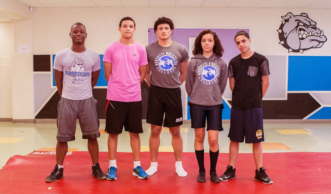 Four student wrestlers pose on a wrestling mat in at Philadelphia's Mariana Bracetti Academy