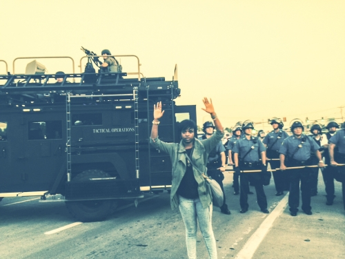 A young woman with short black hair standing, hands upraised, in front of a unit of armed police prepared for a riot.