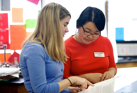 Two young women working together on a document in a classroom.