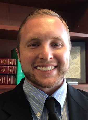 A close head shot of a young man with short blond hair and a short beard smiling in front of a bookshelf, wearing a black blazer, light blue shirt, and black tie.
