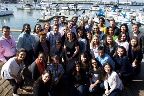 A posed group shot of Teach for America teachers smiling on a pier.