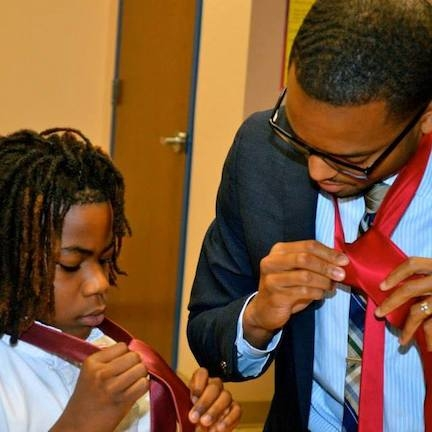 Justin continues to teach today. Here he helps a young mentee learn how to tie a tie.