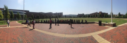 A panorama of two instructors addressing many students sitting on the wall of a brick courtyard in front of a large green field.