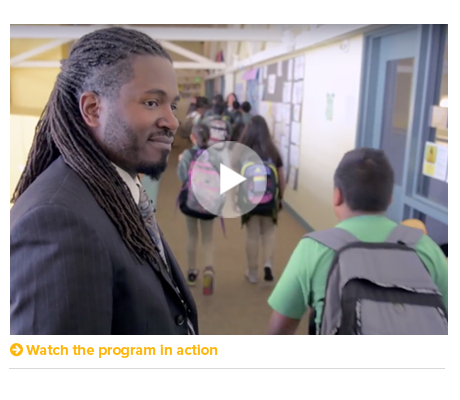 Screenshot from a video showing a male teacher with black dreadlocks smiling in a hallway full of students.