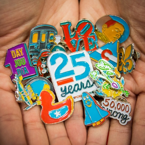 Close shot of a pair of hands held together, palms up, holding a number of different, colorful lapel pins.