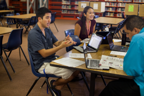 A young adult male sits behind a laptop in a library; he's joined by another male and a young adult female, both with laptops too.