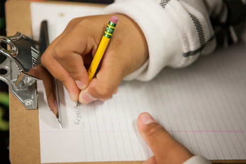 A close-up photo of a student holding a pencil, writing on a clipboard.