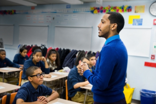 Teacher in a bright blue sweater stands in front of a class of middle school aged students, who are all watching him closely; classroom walls decorated with student work are in the background.