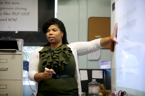 Young adult female teacher wearing a green dress stands in front of a classroom pointing to a white board