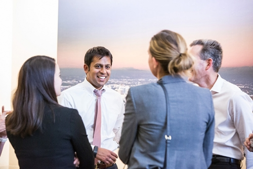 Photo of 4 young adults - two men & two women - standing together in an office, they are all wearing business professional clothing and looking at each other