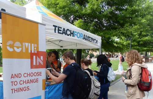 A group of young people standing at a Teach For America recruitment booth on a college campus.
