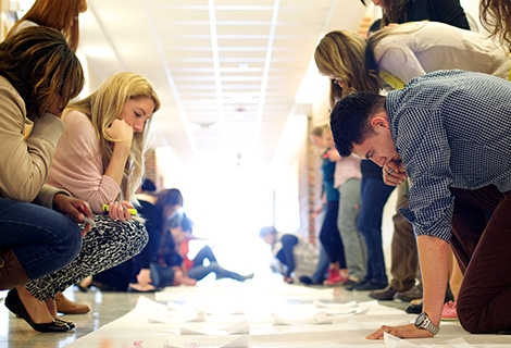 A group of young people crouched around a large piece of paper, working together on an exercise.