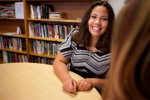 Photo of a smiling young adult female sitting at a table talking with another female; bookcases full of books are in the background