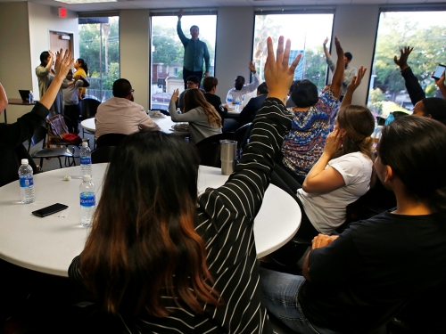 A group votes by raising hands