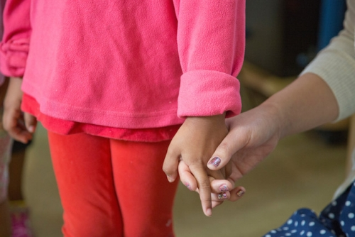 A teacher holds hands with a young Latina student.