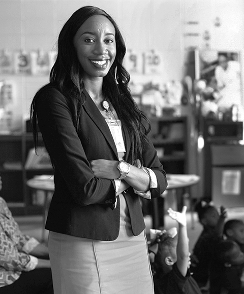 Photo of an African American woman standing proudly in front of a classroom.