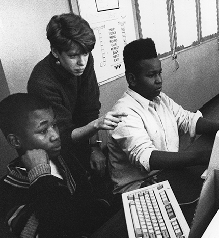 A black and white photo of a Teach For America teacher working with students in the early 90s.