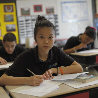 A high-school-aged girl in a black shirt with thick straight black hair tied up, in a classroom, looking up from her work.