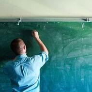 A Teacher Writing on a Chalkboard