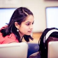 A teacher instructs her student at a computer.