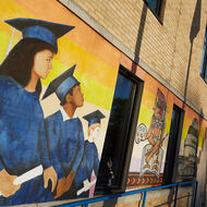 A mural of students in graduation gowns.