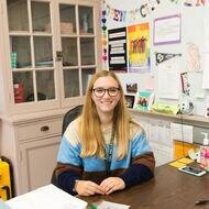 Teacher sitting at desk smiling