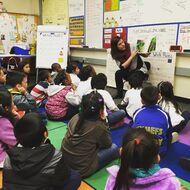 Claire Baugher (2014) reading to a class of students